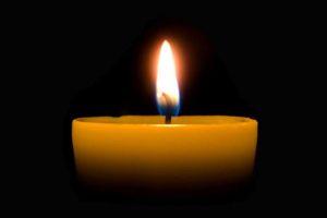 Zapalona świeca na czarnym tle