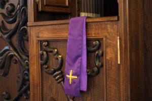 drzwiczki konfesjonału, przez które przewieszono fioletową stułę