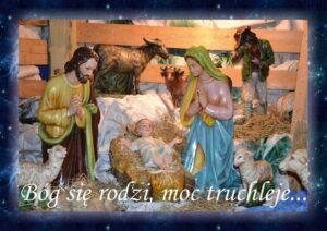 Stajenka bożonarodzeniowa. Figurki świętego Józefa, Maryi i Dzieciątka Jezus w żłóbku. Napis Bóg się rodzi, moc truchleje
